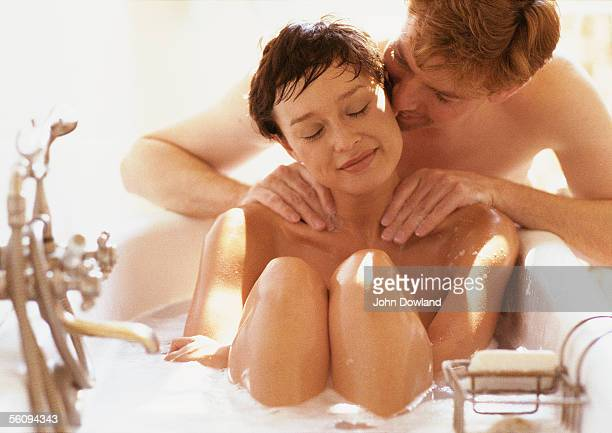 woman taking bath, man massaging her shoulders - sensual massage stock photos and pictures