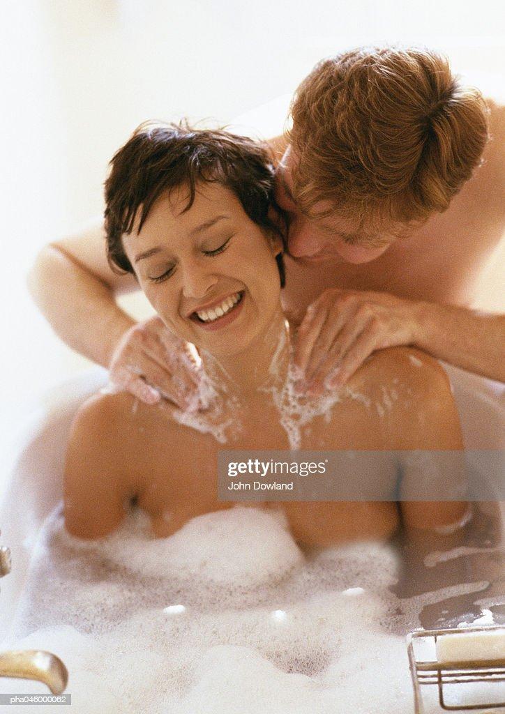 Woman taking bath, man massaging her shoulders : Stockfoto