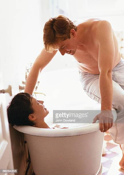 Woman taking bath, man sitting on side of bathtub, looking down at woman