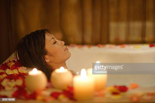 woman taking bath, with candles and flower petals. - aromatherapy stock pictures, royalty-free photos & images