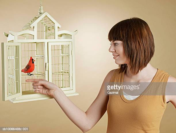 Woman taking bird out of cage