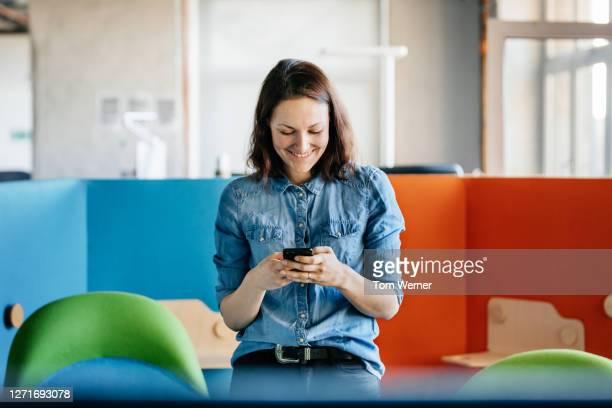 woman taking break from work using smartphone - buntes hemd stock-fotos und bilder