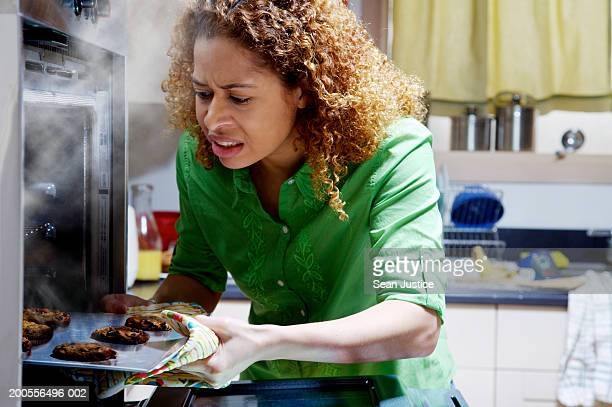 woman taking burnt cookies from oven - burnt stock pictures, royalty-free photos & images