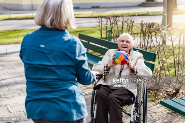 woman taking care of old woman in wheelchair playing with ball in park - hingabe stock-fotos und bilder