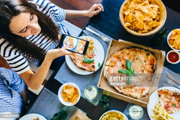 Woman taking cell phone picture of pizza on table