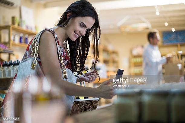 Woman taking cell phone picture of product in shop