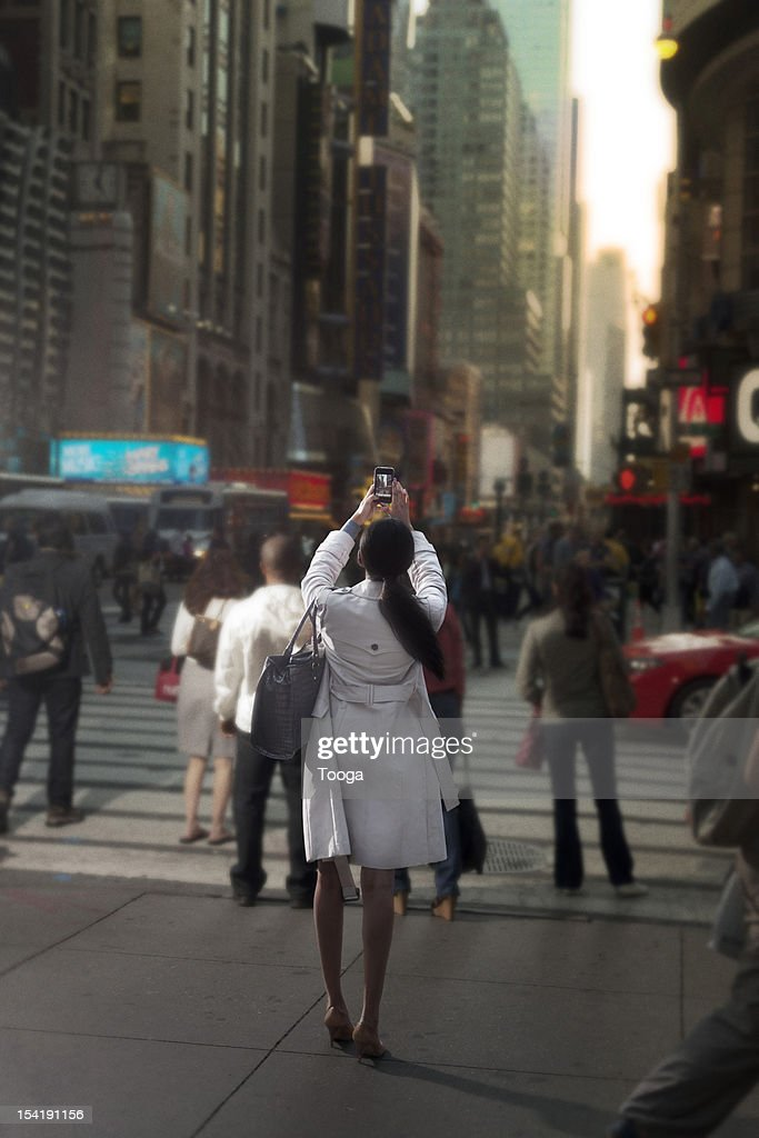 Woman taking cellphone picture of Times Square : Stock Photo