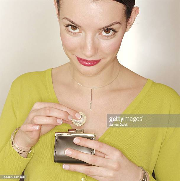 Woman taking coin out of purse, portrait