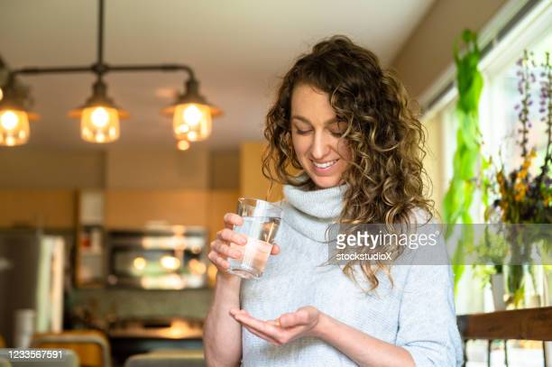woman taking daily supplements or medication - vitamin stock pictures, royalty-free photos & images