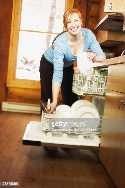 Woman taking dishes out of dishwasher