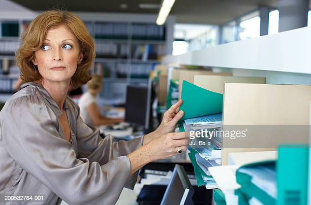 Woman taking file from shelf in office, looking over shoulder
