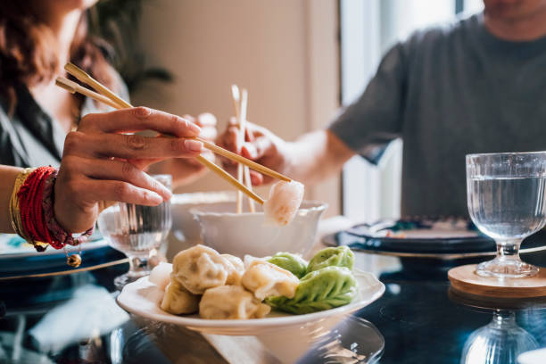 Woman taking food with chopsticks while sitting by man at home