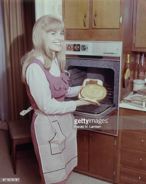 Woman Taking Fresh Pie Out Of Oven