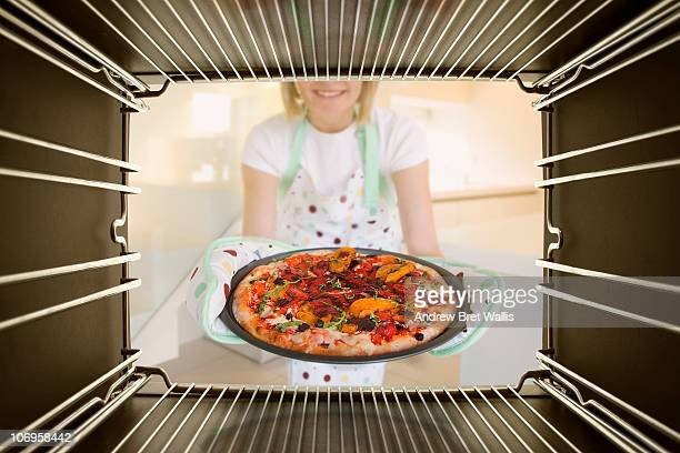 woman taking freshly baked pizza out of an oven