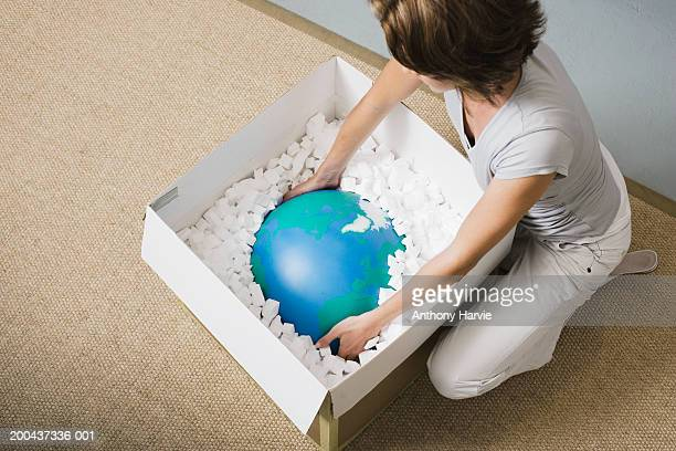 Woman taking globe from box, overhead view