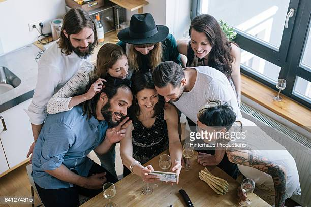 Woman taking group selfie at party