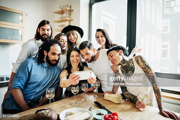 woman taking group selfie at party - middelgrote groep mensen stockfoto's en -beelden