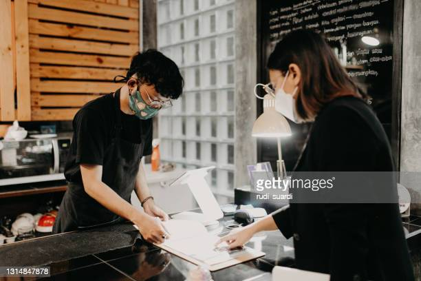 woman taking his order at a coffee shop - indonesia stock pictures, royalty-free photos & images