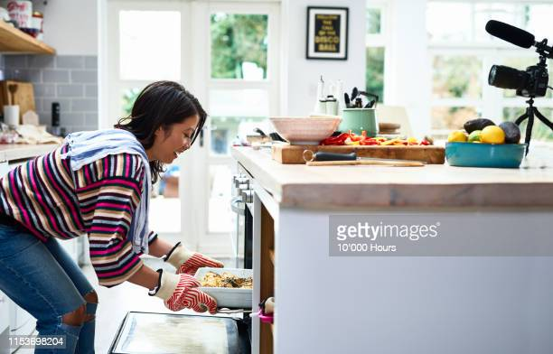 woman taking home baked meal out of oven - healthy eating stock pictures, royalty-free photos & images