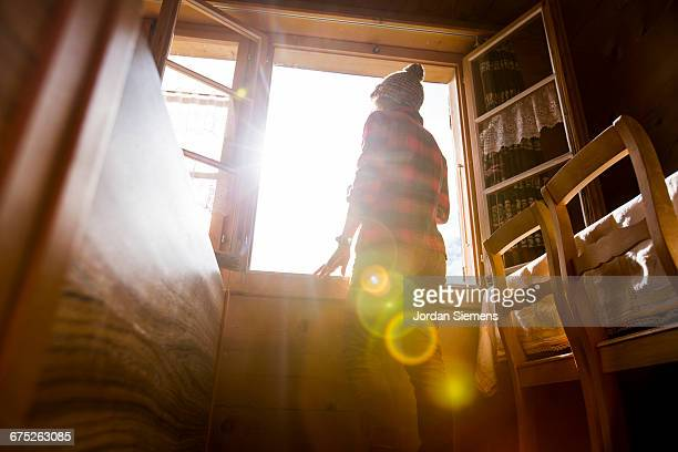a woman taking in the view form her room - morgen stock-fotos und bilder