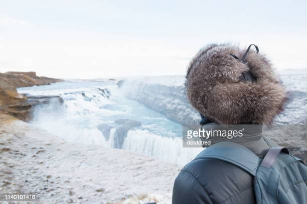 woman taking in view, gullfoss waterfall, located in the canyon of hvita river in south west iceland - fur hat stock pictures, royalty-free photos & images