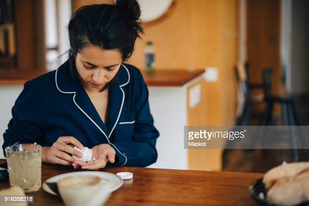Woman taking medicine during breakfast while sitting at table
