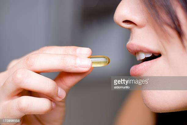 woman taking medicine - girls open mouth stockfoto's en -beelden
