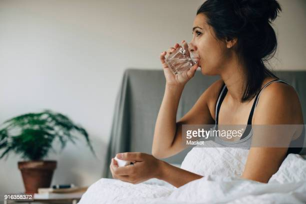 woman taking medicine while sitting on bed at home - routine stock-fotos und bilder