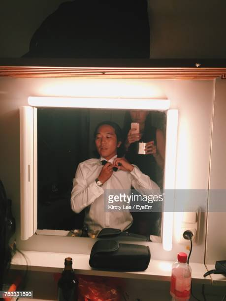 Woman Taking Mirror Selfie While Man Getting Ready In Dressing Room At Backstage