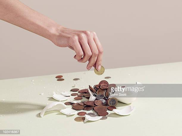 woman taking money from a broken piggy bank - picking up stock pictures, royalty-free photos & images