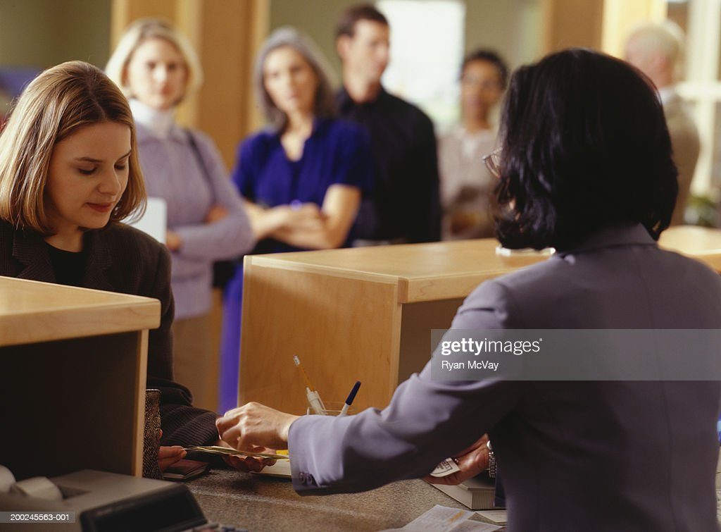 Woman Taking Money From Bank Teller In Bank Stock Foto Getty Images