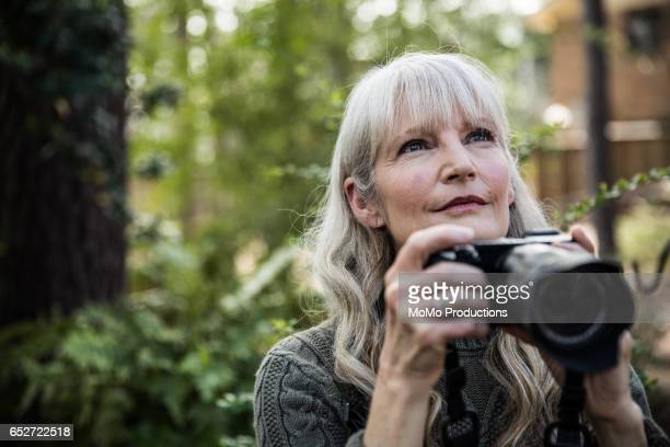 woman taking nature photographs outdoors - hobbies stock pictures, royalty-free photos & images