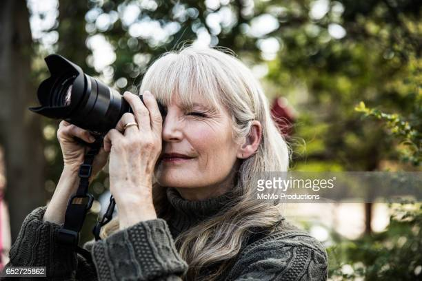 Woman taking nature photographs outdoors