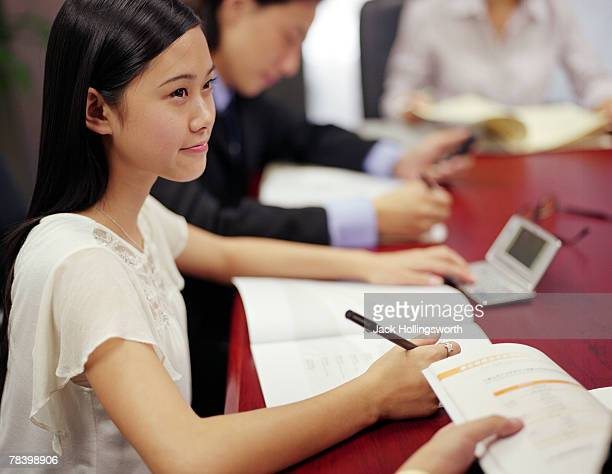 Woman taking notes in business meeting