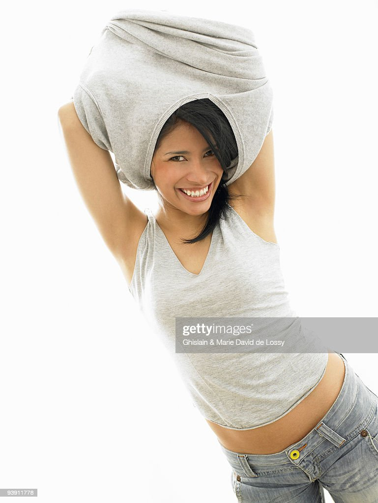 Woman taking off her sweater : Stock Photo