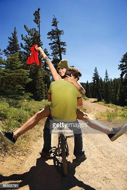 Woman taking off top while man embraces her on mountain bike