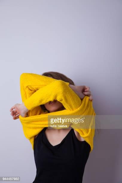 Woman taking off yellow sweater in studio