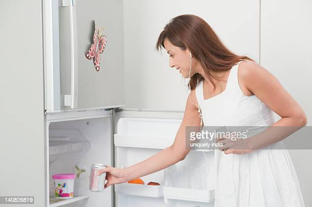 Woman taking out a drink can from a refrigerator and listening to an MP3 player