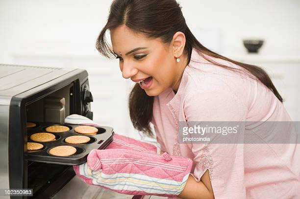 Woman taking out baked cookies from a microwave oven