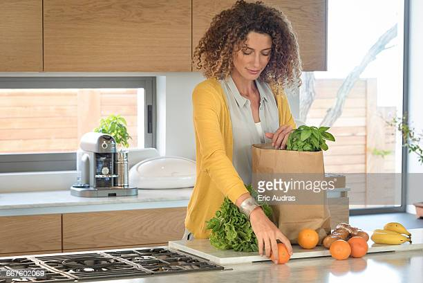 Woman taking out food from a paper bag in the kitchen