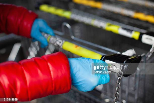 woman taking out shopping cart, wearing protective gloves - infectious disease stock pictures, royalty-free photos & images