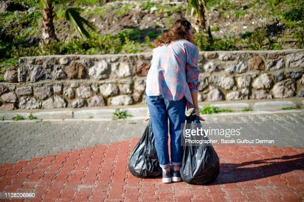 a woman taking out the garbage - absence stock pictures, royalty-free photos & images