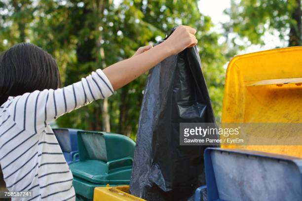 woman taking out the trash - waste management stock pictures, royalty-free photos & images