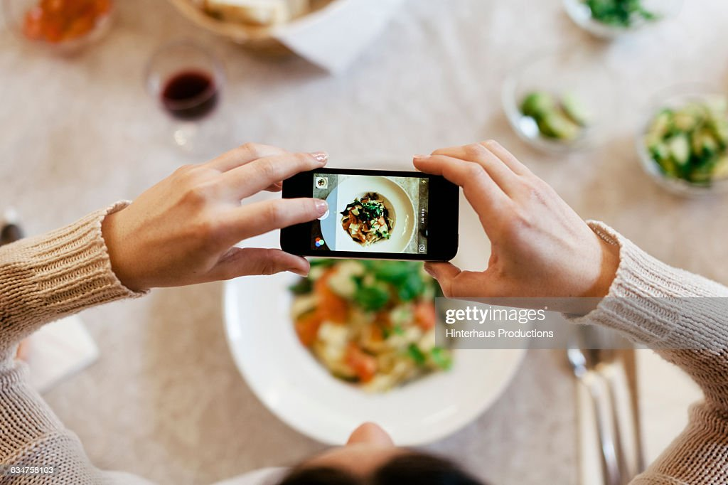 Woman taking overhead photo of dinner : Stock Photo