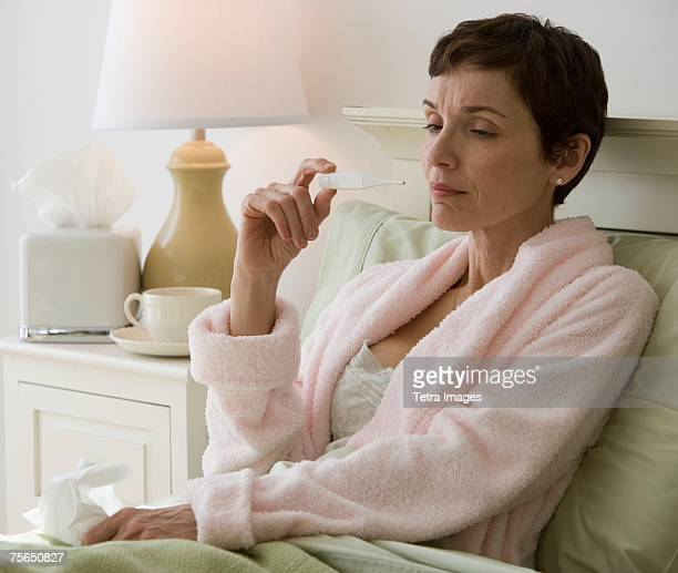 Woman taking own temperature in bed