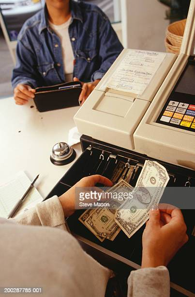 Woman taking payment at fast food restaurant, close up of cash register