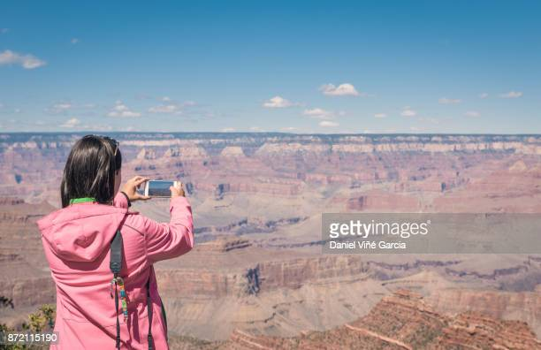Woman taking photo at the Grand Canyon, Arizona.