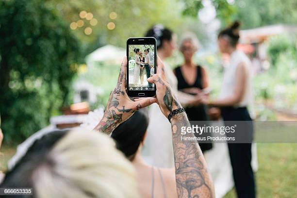 woman taking photo at wedding - hochzeit fotos stock-fotos und bilder