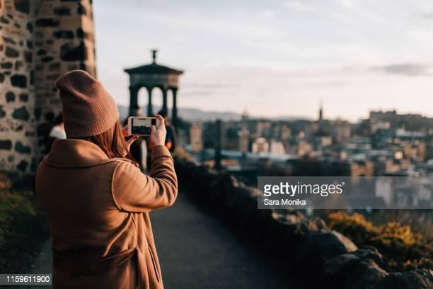 woman taking photo from calton hill, edinburgh, scotland - カールトンヒル ストックフォトと画像