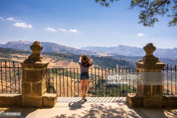 mujer tomando fotos desde la cima de la montaña en el parque alameda del tajo en ronda, españa - moruno fotografías e imágenes de stock